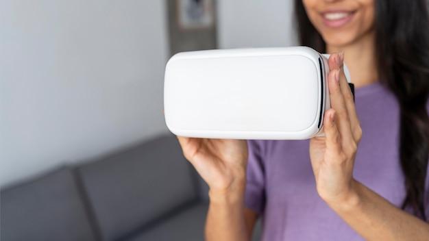 Buźka kobieta trzyma zestaw słuchawkowy wirtualnej rzeczywistości