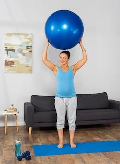 Buźka kobieta w ciąży w domu szkolenia na matę z piłką