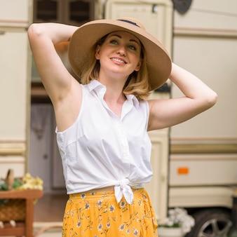 Buźka kobieta w kapeluszu ciesząca się podróżą z przyczepą kempingową