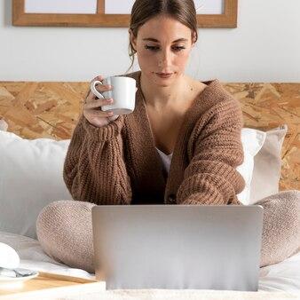Buźka kobieta w łóżku pracuje