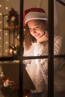 Buźka kobieta z santa hat przez okno patrząc na tablet