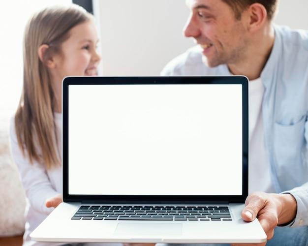 Buźka mała dziewczynka i ojciec trzyma laptopa