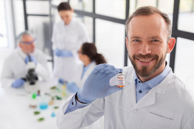 Buźka naukowiec trzymając fiolkę