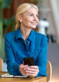 Buźka starsza kobieta trzymając smartfon podczas pracy
