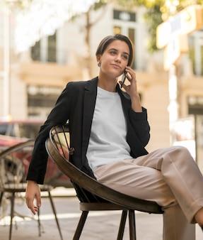Buźka stylowa kobieta rozmawia przez telefon na zewnątrz