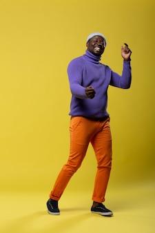 Być aktywnym. zadowolony młody człowiek demonstruje swój uśmiech, stojąc na żółtym tle