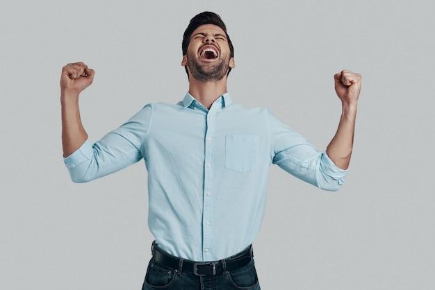 Być najlepszym! przystojny młody mężczyzna uśmiecha się i gestykuluje stojąc na szarym tle