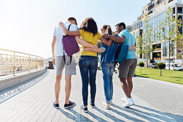 Być razem. radosnych młodych ludzi obejmujących się i stojących plecami do kamery, idąc prosto