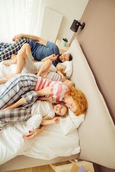 Być razem. widok z góry na szczęśliwą, miłą rodzinę leżącą razem w łóżku