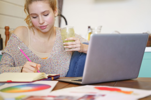 Być zajętym. zadowolona kobieta trzymająca szklankę, patrząc na swój zeszyt