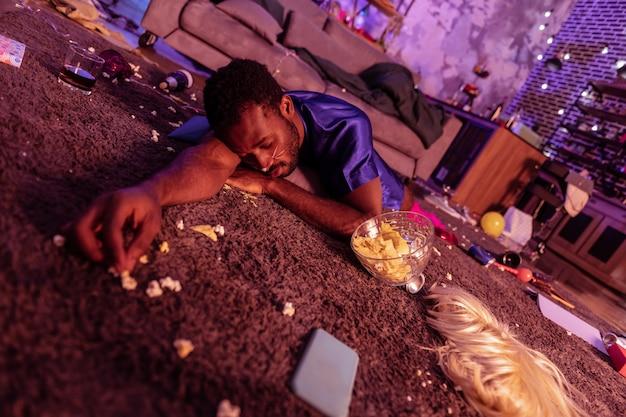 Bycie ekstremalnie pijanym. pijany i nietrzeźwy afroamerykanin nie dociera do sypialni i spędza noc na brudnym dywanie