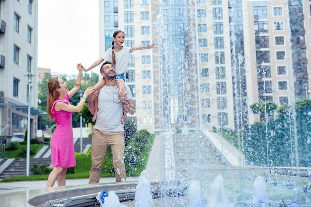 Bycie silnym. miły radosny mężczyzna trzymający córkę na ramionach podczas wspólnego spaceru z rodziną