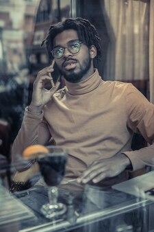 Bycie we wszystkich uszach. zadowolony brodaty mężczyzna w okularach podczas pracy na odległość