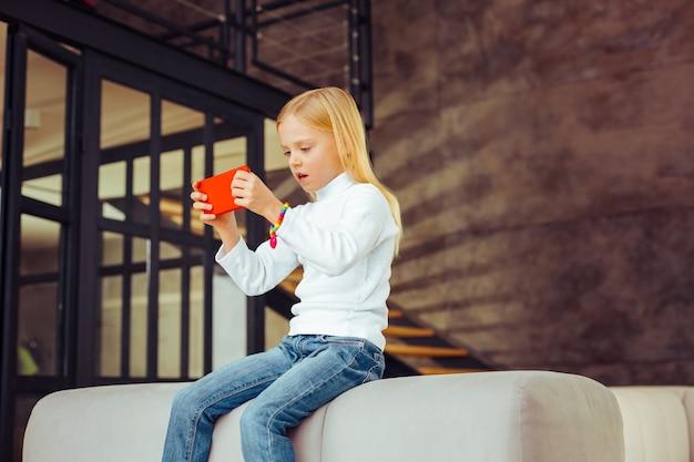 Bycie zaskoczonym. dość mała kobieta jest uważna podczas grania w grę online