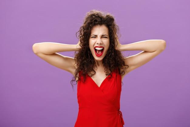 Były chłopak zepsute kobieta formalne wydarzenie jest oburzona i wkurzona, krzycząc w furii, trzymając się za ręce na kręconych włosach, krzywiąc się ze złości, stojąc na fioletowym tle w stylowej wieczorowej czerwonej sukience.