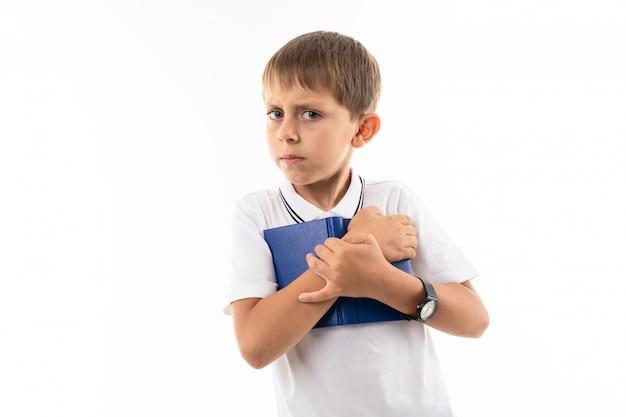 Bystry chłopak przycisnął białą książkę do piersi
