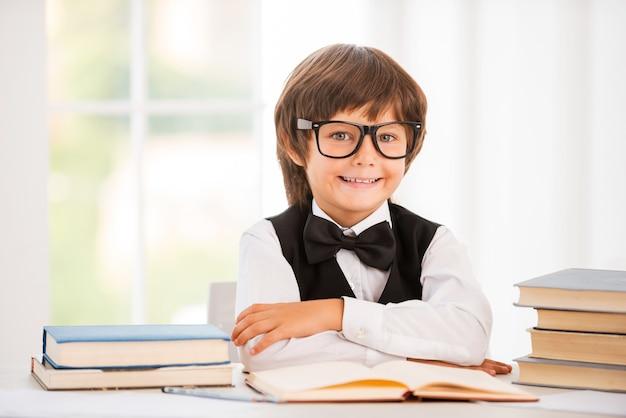 Bystry i pewny siebie uczeń. śliczny młody chłopak trzymający skrzyżowane ręce siedząc przy stole