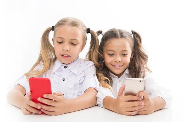Bystrzy uczniowie. mali uczniowie wysyłają sms-y podczas zajęć na białym tle. śliczni uczniowie liceum zanurzają się w lekcjach smartfonów. mali uczniowie korzystający z telefonów komórkowych w klasie.