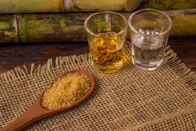Cachaca to nazwa typowego napoju alkoholowego produkowanego w brazylii z trzciny cukrowej. tradycyjny napój z brazylii na drewnianym stole