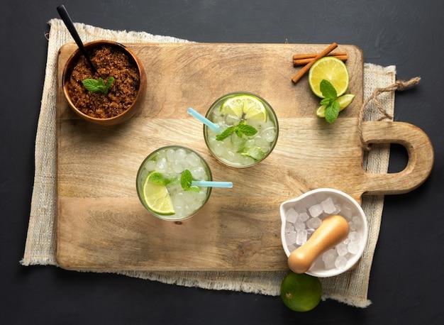 Caipirinha, limonka, świeża mięta, brązowy cukier i kruszony lód. widok z lotu ptaka