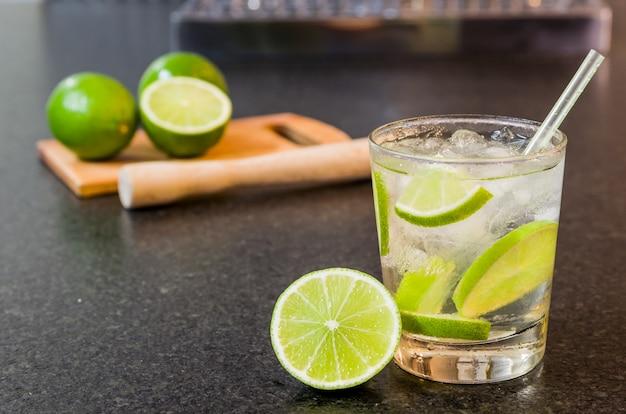 Caipirinha, tradycyjny brazylijski napój alkoholowy, typowy napój na bazie cukru, cytryny, destylowanej trzciny cukrowej (cachaca) i lodu. składniki i napój na czarnej granitowej powierzchni.