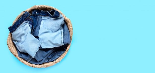 Cajgi w pralnianym koszu na błękitnym tle.