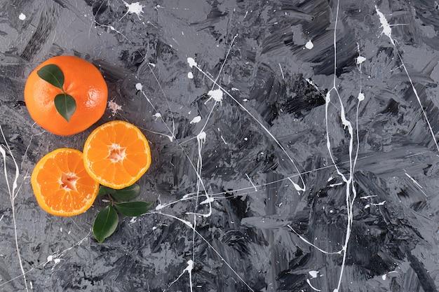 Cała i pokrojona mandarynka na stole mieszanym.