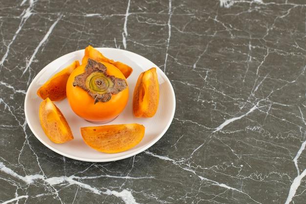 Cała i pokrojona persimmon na białym talerzu.