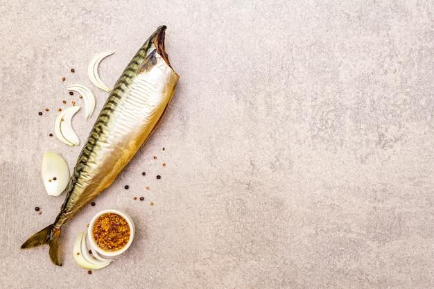 Cała makrela wędzona. musztarda dijon, cebula, czarny pieprz, kolendra. na kamiennym tle