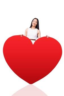 Cała moja miłość jest dla ciebie. piękna młoda azjatka w ładnej sukience, opierając się na wielkiej walentynce w kształcie czerwonego serca i uśmiechając się, stojąc na białym tle