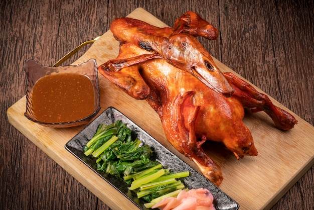 Cała pieczona kaczka miodowa z sosem i warzywami podawana na starym drewnianym stole, pieczona kaczka tradycyjna chińska kuchnia.