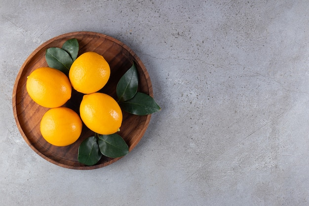 Cała pomarańcza z liśćmi umieszczona na drewnianym talerzu.