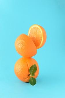 Cała pomarańcza z zielonym liściem, a na nim pomarańcza przecięta na pół na niebieskim tle. koncepcja lato cytrusowe, orzeźwiający sok owocowy. wibrujące kolory.