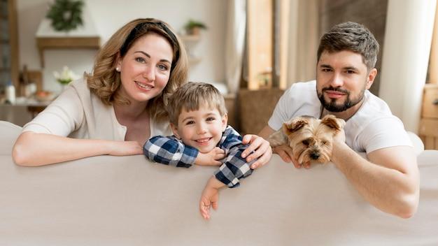 Cała rodzina z psem siedzącym na kanapie