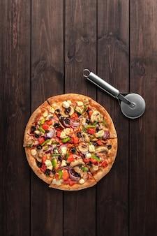 Cała świeża okrągła pizza z mięsem z kurczaka, warzywami, grzybami, serem i nożem widok z góry na drewnianym brązowym stole. smaczna powierzchnia fast food w pizzerii z miejscem na kopię