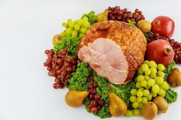 Cała szynka wieprzowa bez kości ze świeżymi owocami. zdrowe jedzenie. posiłek wielkanocny.