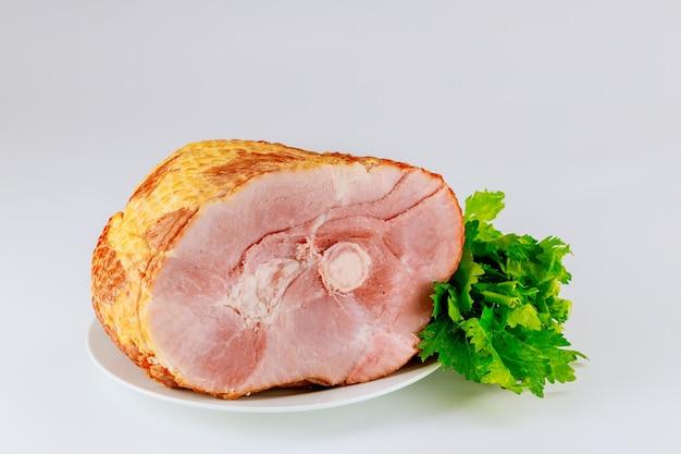 Cała szynka wieprzowa z świeżym selerem na białym tle. danie wielkanocne.