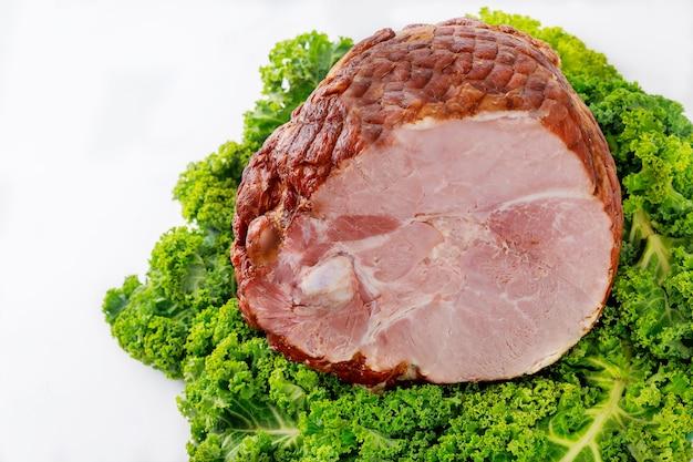Cała szynka wieprzowa ze świeżym jarmużem. zdrowe jedzenie. posiłek wielkanocny.