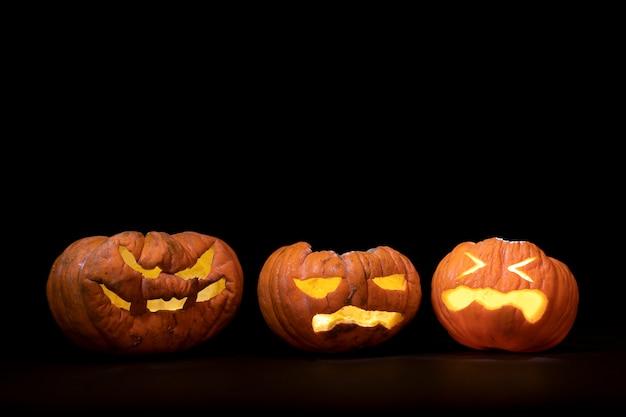 Calabazas de halloween con expresiones terrorificas y fondo de luces