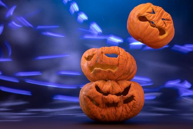 Calabazas talladas para halloween con fondo negro y luces de colores