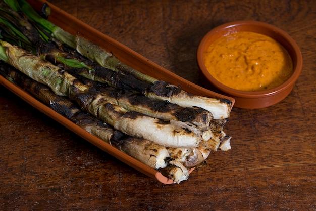 Calçots podane na płytce z sosem romesco na drewnianym stole