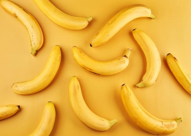 Całe banany ze skórką na żółtej powierzchni