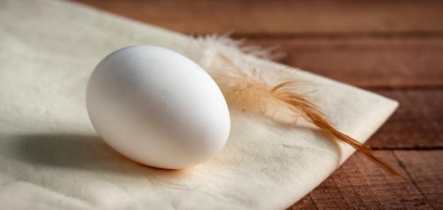 Całe białe jajko z piórkiem na białej serwetce, na drewnianym stole.