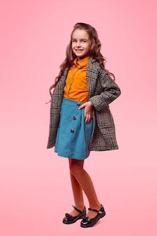 Całe body uroczej uśmiechniętej uczennicy w codziennym ubranku i stylowym płaszczu w kratkę przedstawiającym sezonową modę dla dzieci na różowym tle