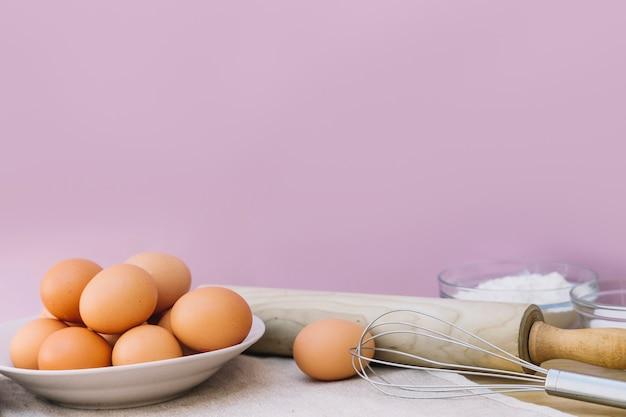 Całe brązowe jaja na talerzu; wałkiem do ciasta i whisks na różowym tle