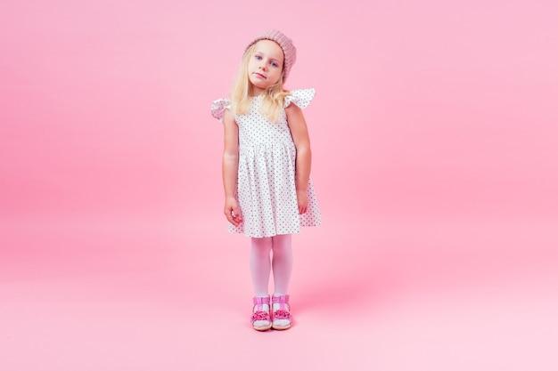 Całe ciało portret uroczej dziewczynki blond dziewczyna niebieskie oczy model w beżowym dzianym różowym kapeluszu w białej sukni księżniczki w grochu jesienny sezon wiosenny w studio strzał na różowym tle