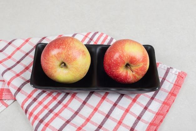 Całe czerwone jabłka na czarnym talerzu z obrusem