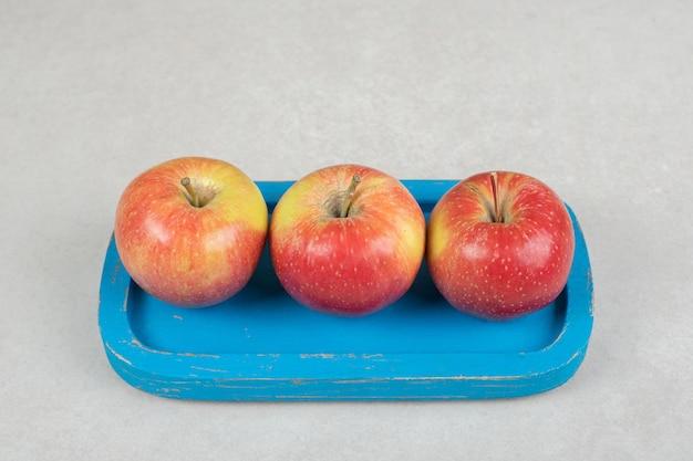 Całe czerwone jabłka na niebieskim talerzu