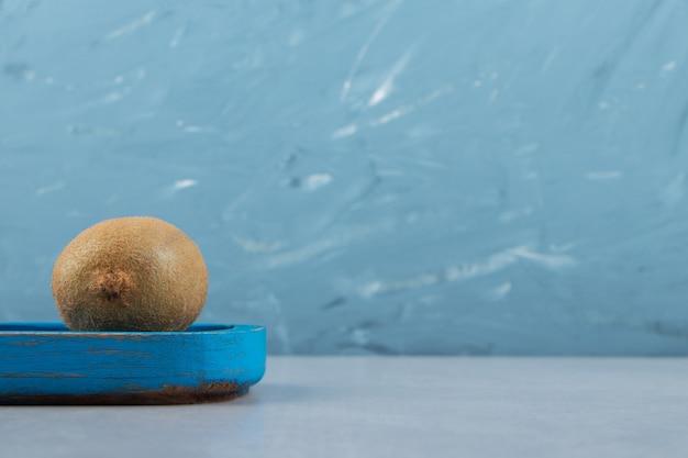 Całe dojrzałe kiwi na niebieskim talerzu
