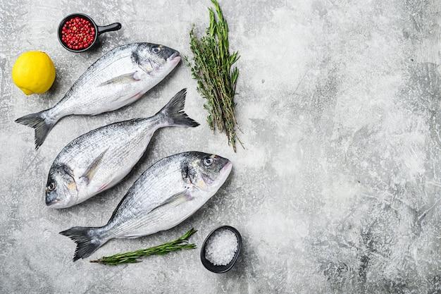 Całe dorado dorada ryby z ziołami do grilla nad teksturą szarym tle widok z góry miejsca na tekst.